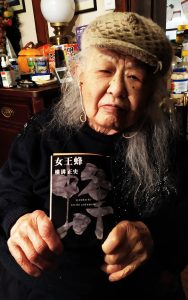 Photo of an elderly woman holding a Japanese detective novel to the camera.